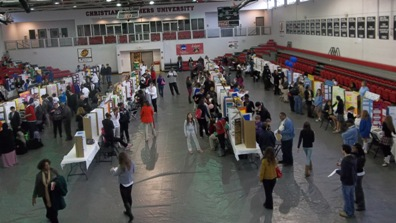 A view looking down on the floor of Canale Arena during the 2013 Memphis-Shelby County Science and Engineering Fair is shown.  In addition to Canale Arena, projects were also displayed in Montesi in Buckman Hall and in the Sabbatini Lounge in the Thomas Center.