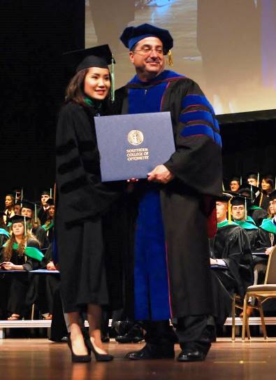 Dr. Carrie Le receiving her diploma.